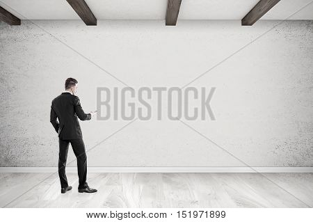 Rear view of businessman with cellphone looking at concrete wall in empty room. 3d rendering. Mockup