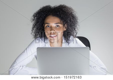 Close up of cheerful office employee sitting at her workplace with laptop in room with gray walls. Concept of high spirits
