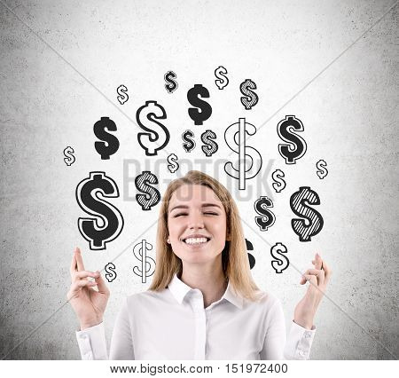 Close up of blond girl with crossed fingers dreaming about money. Dollar signs are drawn at concrete wall behind her. Mock up