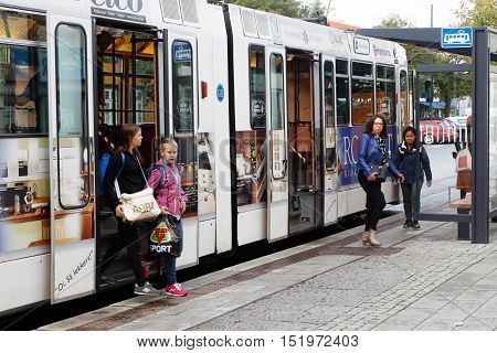 Trondheim, Norway - Sepember 30, 2016: Passengers get off an articulated tram at the tram stop on St. Oloavs gate in Trondheim city center.