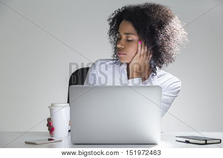 Close up of bored office employee sitting at her workplace with laptop in room with gray walls. Concept of dull life