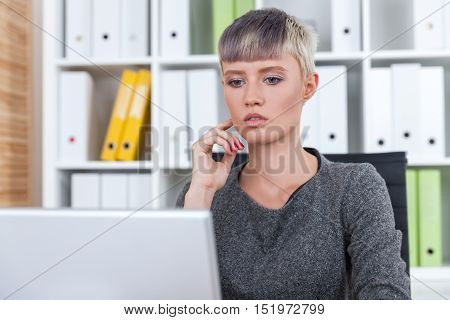 Pensive office worker is looking at laptop screen and thinking about business. Concept of planning and strategic thinking