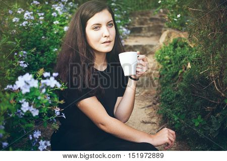 Young smiley woman is drinking floral tea in her garden and dreaming about plans for the future. Feeling harmony with life and nature