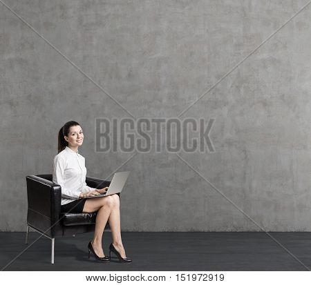 Smiling young woman in leather armchair is sitting near blank concrete wall. Concept of business person. Mock up