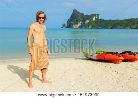 a young topless man standing in front of a row of Kayaks canoes boats on the PhiPhi Don beach in Thailand