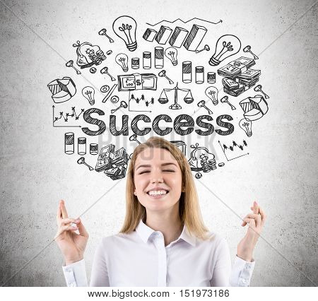 Blond smiling woman with crossed fingers is standing against concrete wall with success sketch on it. Concept of believing in yourself