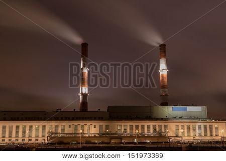Factory with two smoke stack against sky at night