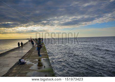Evening fishing on a pier. Riga, Latvia