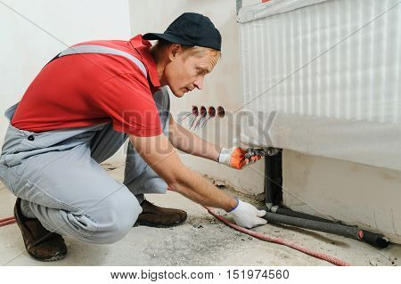 Installation of home heating. Worker attaches the pipe to the radiator.
