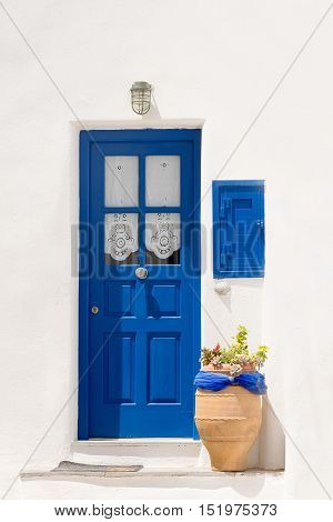 Beautiful  blue door with a pot outside at Paros island in Greece. A traditional cyclades outside of a house.