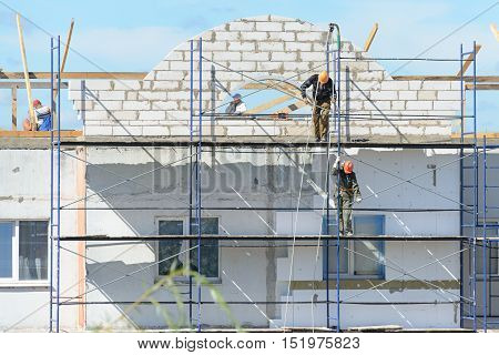 Workers Builders Lift Building Materials On Scaffolding