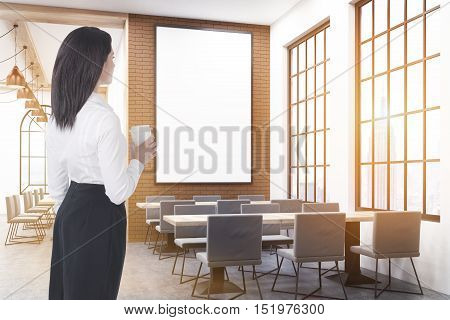 Rear view of businesswoman with paper coffee cup standing in coffee shop and looking at the interior. Mock up. Toned image. 3d rendering