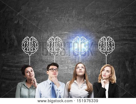Group of people of different gender and ethnicity is standing against blackboard and thinking. Four brain sketches are drawn above their heads. Concept of focus group. Mock up