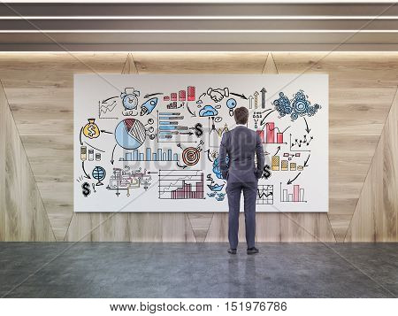 Rear view of man looking at startup sketch on whiteboard in room with wooden walls. Concept of business education. 3d rendering.
