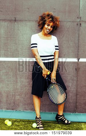 young stylish mulatto afro-american real girl playing tennis, sport healthy lifestyle people concept