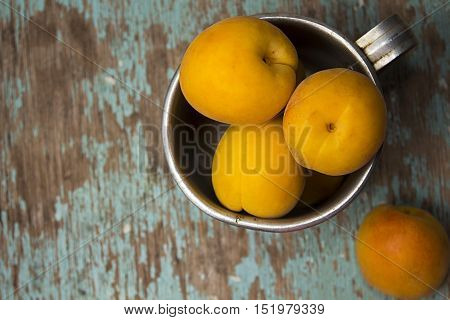 Apricots In  Aluminum Mug On Rustic Wooden Surface.
