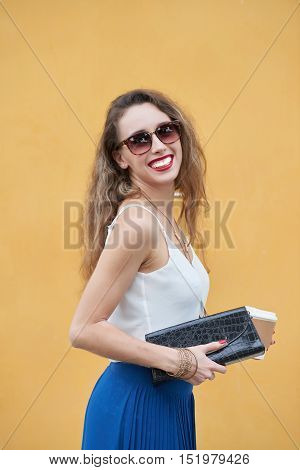 Cheerful young woman with clutch and coffee cup