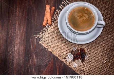 White cup of coffee brown sugar and cinnamon on a brown wooden table top view