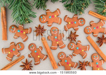 Many gingerbread men on a grey board and Christmas fir tree