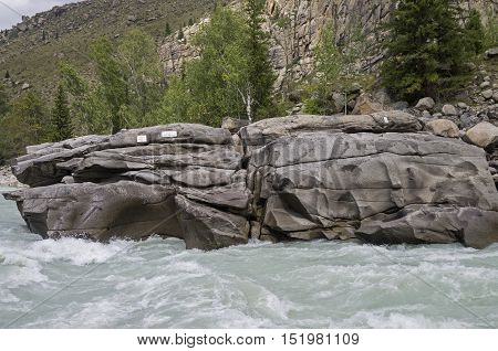 Stone at the end of a rapids with with plaque in memory of dead tourists. Rapids