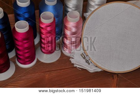 Multi-colored thread and white fabric in the hoop for the embroidery and sewing