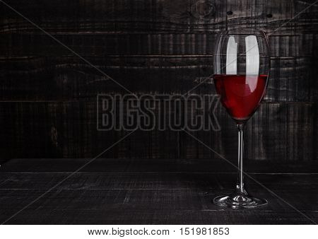 Glass of red wine with reflections on wooden board background
