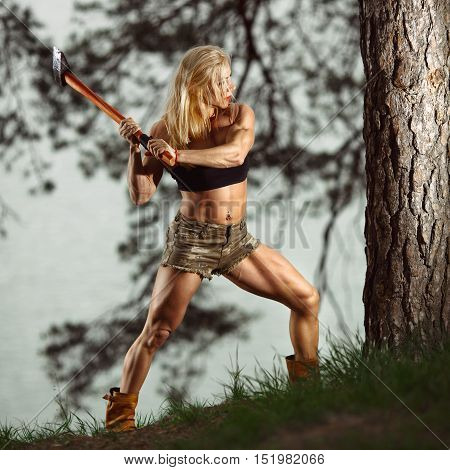 Muscular woman chopping a tree. Fitness woman lumberjack