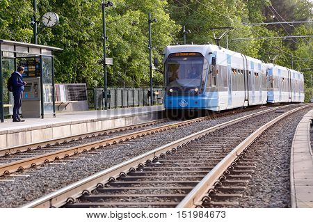 Stockholm, Sweden - June 9, 2016: A person waiting when a blue tram arriving at the tram stop Linde at the tramway Tvarbanan in Stockholm public tranport system.