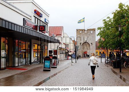 Visby, Sweden - May 15, 2016: People at downtown Visby in Ostercentrum with the Osterport gate with a hosted Swedish flag on the city wall tower in the background on rainy day.