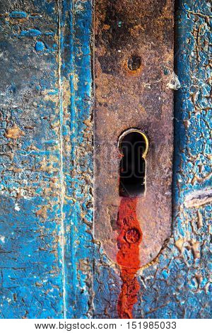 Bloody keyhole lock on a old rusty cracked blue wooden door