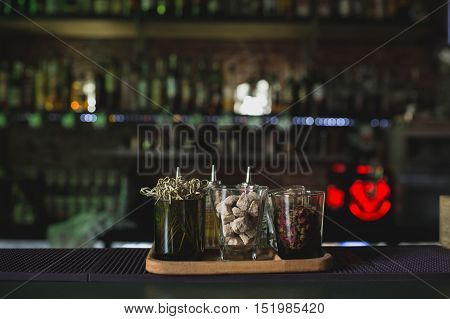 Glasses on bar table, refreshing drinks with straws. Shugar and other Supplements for Closeup of three creative sweet exotic non-alcoholic party cocktails in restaurant at bar background.