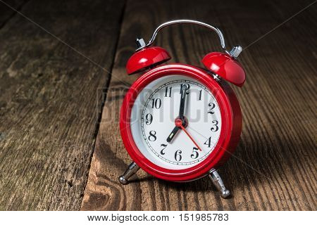 Red alarm clock at seven oclock on the wooden table