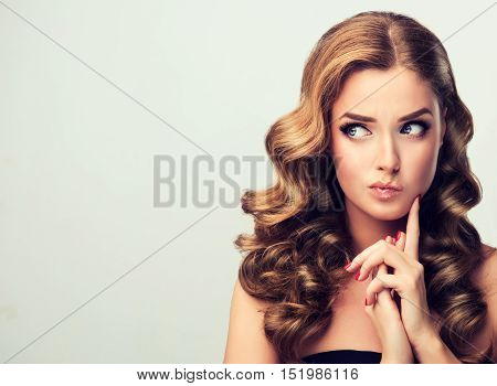 Frowning, the woman looks away with disbelief thinking .Beautiful girl with curly hair with expressive facial expressions