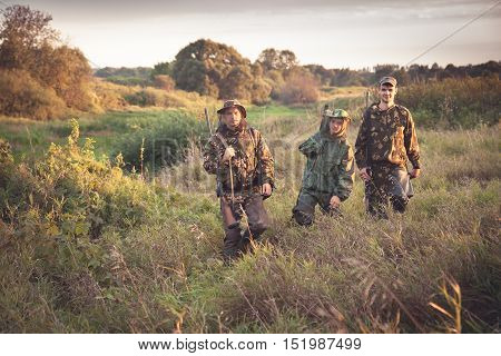 Hunters going through tall garass in rural field at dawn during hunting season