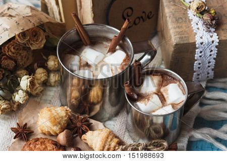 Metal mugs with cacao and marshmallow with different cookies soft focus background