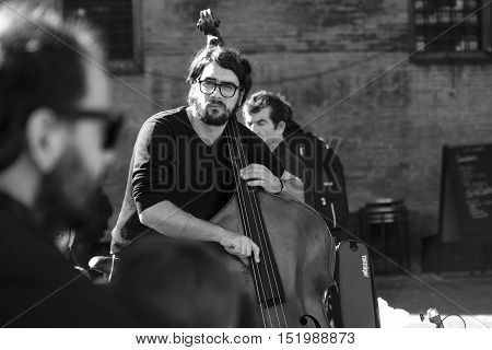 Bologna Italy October 15 2016 - black and white still of a contrabass street performer while playing for the passers