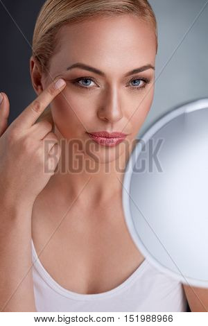 Beautiful woman with mirror looking her perfect skin