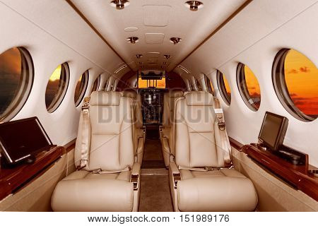 Luxury interior in bright colors of genuine leather in the business jet, sunset and clouds through the porthole