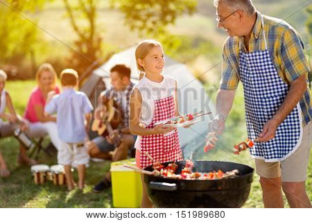 smiling grandfather giving granddaughter grilling meat for dinner