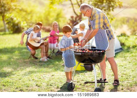 grandfather giving grandson barbecue food for family