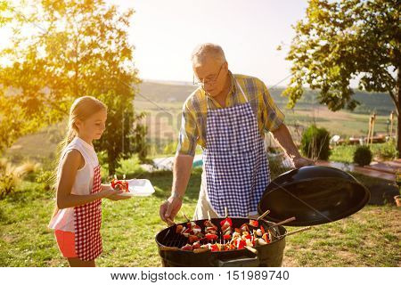 Grandfather and granddaughter preparing barbecue in countryside