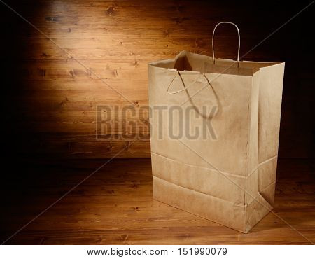 Empty paper grocery bag on wooden background with place for text
