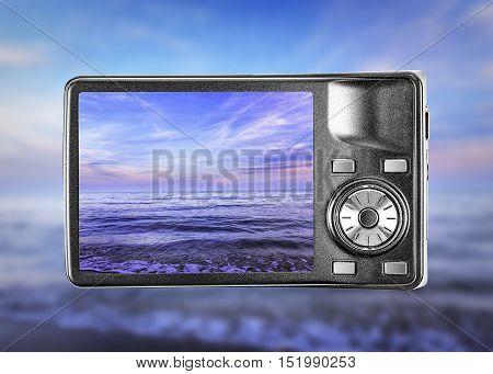Digital photo camera, taking picture of beautiful seaside.