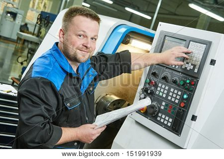 industrial worker operating cnc turning machine in metal machining industry