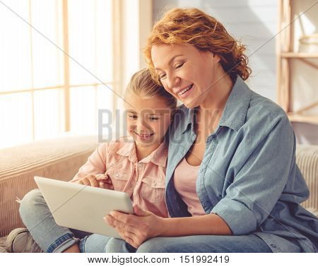Cute little girl and her beautiful grandma are using a digital tablet hugging and smiling while sitting on couch at home
