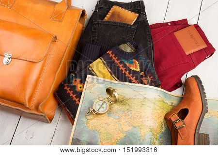 Travel Concept - Bag, Shoe, Jeans, Geographic Map, Passport, Compass, Purse On White Wooden Table