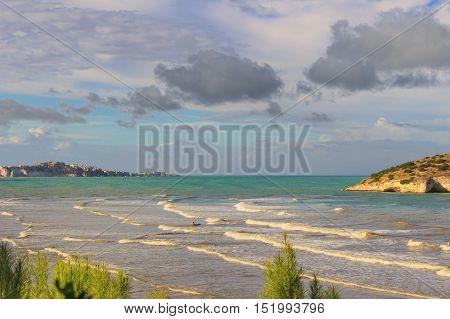 Summertime.Gargano coast: Portonuovo beach,Vieste-(Apulia) ITALY-In the background the Gattarella islet or Portonuovo rock and Vieste town.