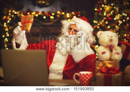 Christmas. Santa Claus with a laptop reading a letter and drinking tea
