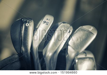 Macro detail of golf irons, sand and loft wedges or irons - sepia toned
