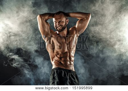 Studio portrait of topless muscular sportsman posing with arms on head and forced smile over smoke black background.